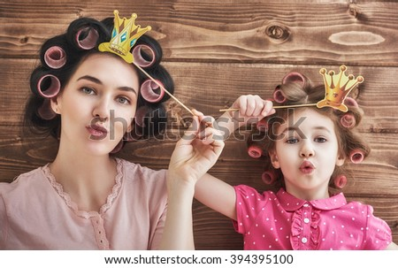 Funny family! Mother and her child daughter girl with a paper accessories. Beauty funny girl holding paper crown on stick. Beautiful young woman holding paper crown on stick. - stock photo
