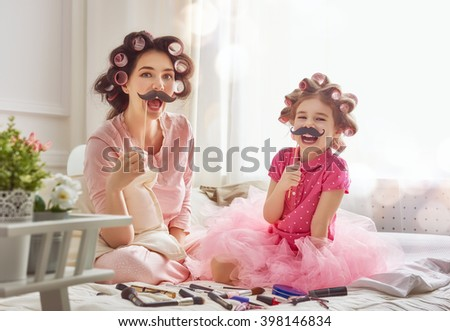 Funny family Mother and her child daughter girl with a paper accessories. Mother and daughter preparing for a party and having fun. Beautiful young woman and funny girl with a paper mustache on stick. - stock photo