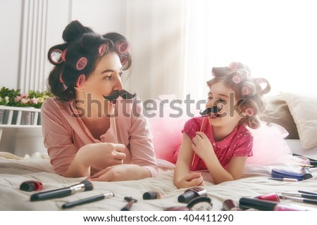 Funny family! Mother and her child daughter girl with a paper accessories. Mother and daughter preparing for a party and having fun. Beautiful young woman and funny girl with a paper mustache on stick - stock photo