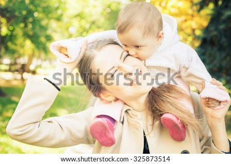 Funny family - mother with her baby outdoor at autumn park. Concept of happy family. A child's itching gums, already growing teeth - stock photo