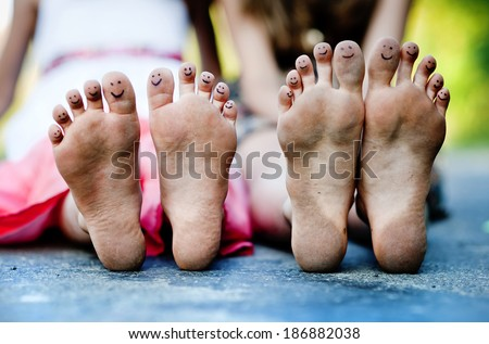 Funny feet of two girls sitting on a pavement in green park - stock photo