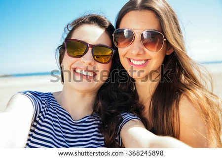 Funny female friends on vacation taking selfies on the beach with a smart phone - stock photo