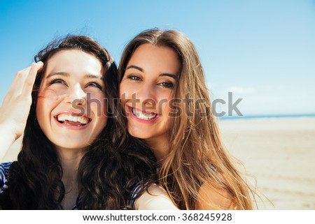 Funny female friends on vacation taking selfies on the beach with a smart phone