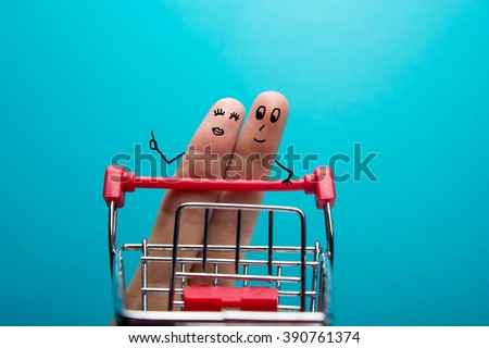 Funny fingers shopping at supermarket with red cart trolley on blue background - stock photo