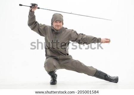 Funny fisherman wearing grey watertight costume and black waders with the spinner posing like ninja. Isolated on white background