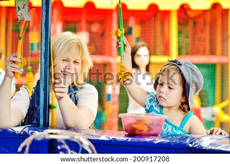 funny fishing of mother and daughter in amusement park - stock photo