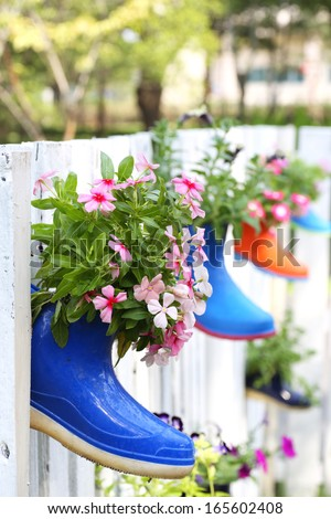 Funny flower decoration set in old rubber boot with wood wall in garden - stock photo