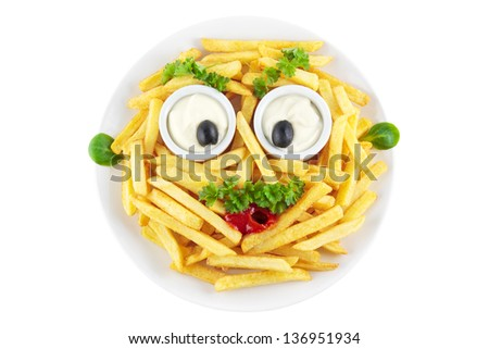 Funny french fries face made of mayonnaise, ketchup, olives and parsley - stock photo