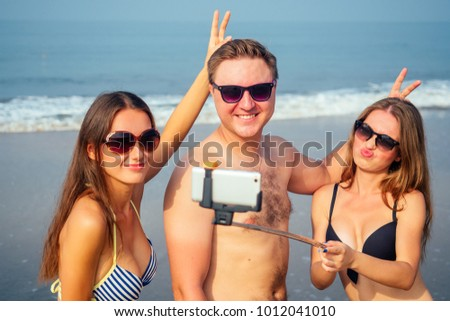 funny friends make a photo on a self-stick on the beach