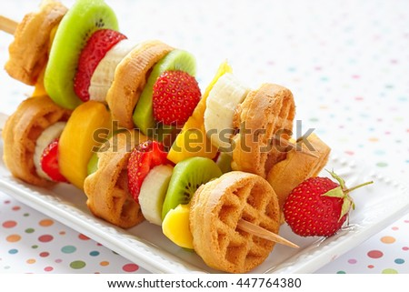 Funny fruits and berries kebab on a dish - stock photo