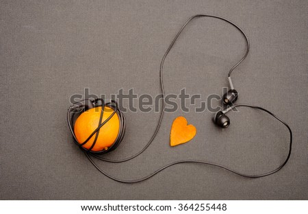 Funny fruity music player: headphones coming from of mandarin forming a heart shape on a black background. Small orange heart lying near him. The gift on Valentine's Day for music and fruit lovers. - stock photo