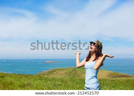 Funny funky woman enjoying nature travel in Asturias coast, Spain. Female on summer or spring leisure vacation towards the sea. - stock photo