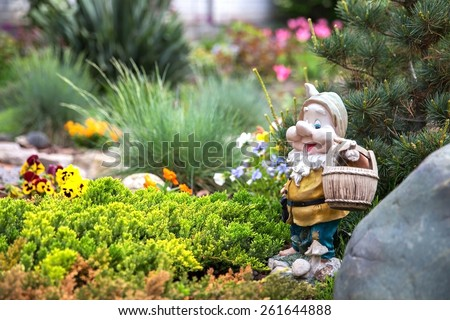 Funny garden gnome standing among nice flowers - stock photo