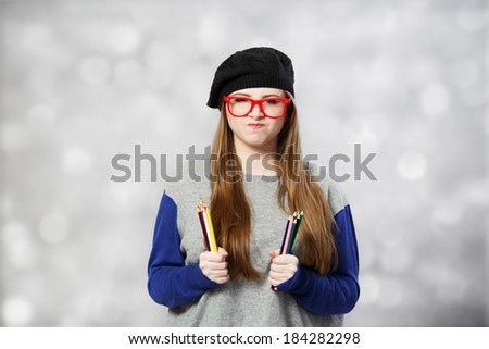 Funny girl at beret holds pencils at both hands at light background