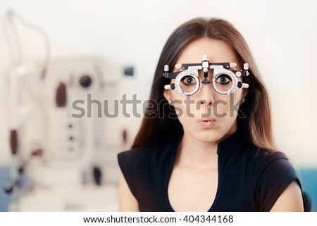 Funny Girl at Ophthalmological Exam Wearing Eye Test Glasses - Surprised woman wearing a Phoropter device  - stock photo