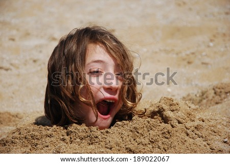 Funny Girl Buried in the Sand at the Beach