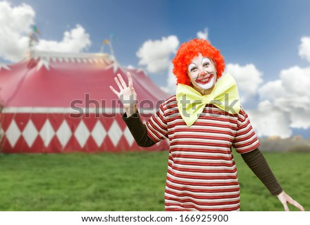 Funny girl clown with big bow tie and makeup over circus tent ...