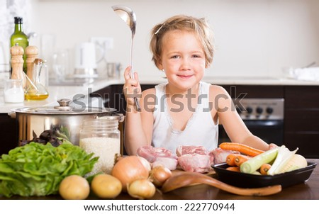 Funny  girl cooking food at kitchen  - stock photo