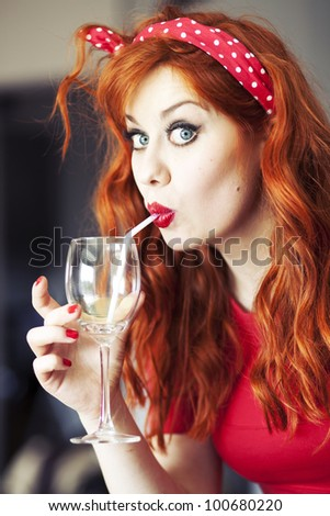 Funny girl drinking wine using straw.