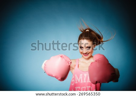 Funny girl female boxer in big fun pink gloves playing sports boxing hair motion studio shot blue background - stock photo