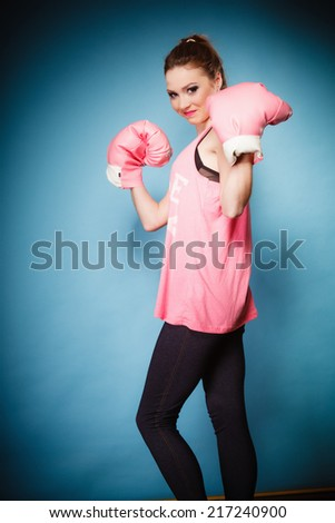 Funny girl female boxer model wearing big fun pink gloves playing sports boxing studio shot blue background - stock photo