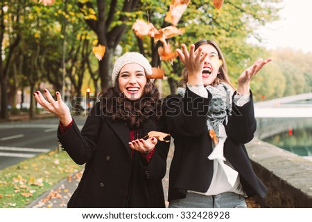 Funny girl friends throwing dry leaves in the city in autumn - stock photo