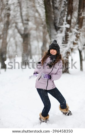 Funny girl having fun in beautiful winter park during snowfall. Happy teenage girl playing with a snowballs on a winter walk in nature. Happy young girl is playing in snow, good winter weather. - stock photo