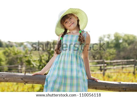 Funny girl in a beautiful dress and hat