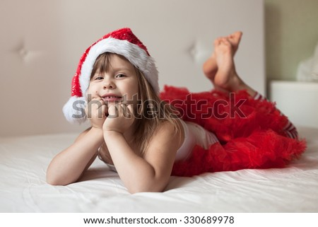 Funny girl in a Christmas cap and red skirt lying on  bed , home new year - stock photo