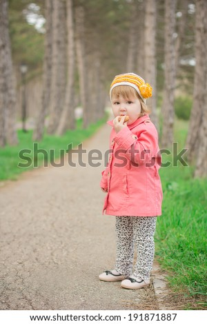 funny girl in a pink coat standing in the park with cookies
