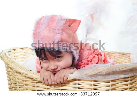 funny girl in a pink suit of a cat sits in a basket - stock photo