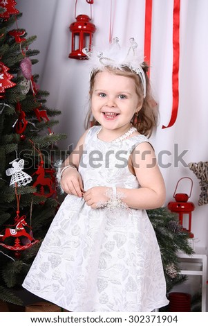Funny girl in a white dress standing near the Christmas tree among the gifts and toys