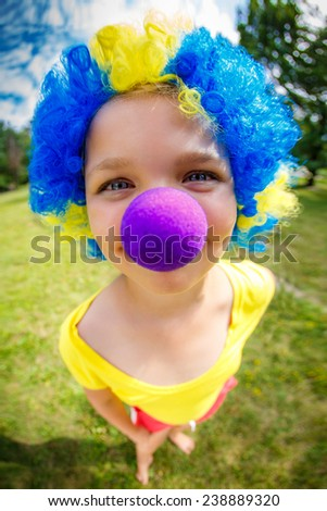 Funny girl in clown wig with blue nose - stock photo