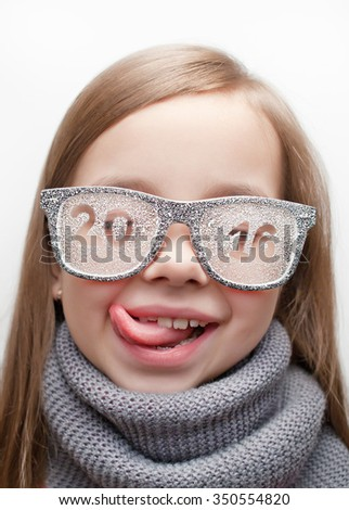 Funny girl in glasses and scarf with the words 2016 shows tongue - stock photo