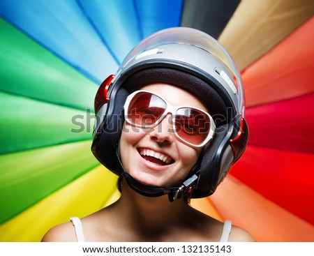 Funny girl in helmet having fun. Multicolored background.