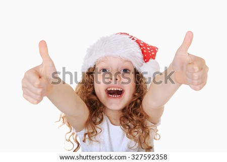 Funny girl in Santa hat showing thumbs up, in light background. Christmas background concept. - stock photo