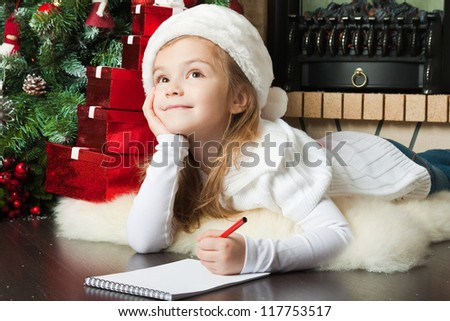 Funny girl in Santa hat writes letter to Santa near christmas tree