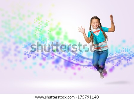 funny girl jumping around colored dots and rays of light