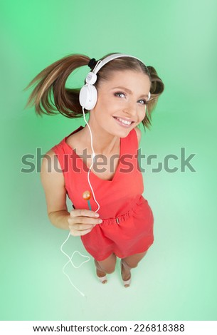 funny girl listening music on green background. top view of woman listening to music on headphones and holding lollipop - stock photo