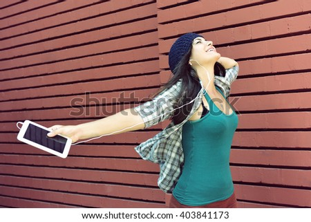 Funny girl listening to the music with earphones from a smart phone over red bricks wall background.