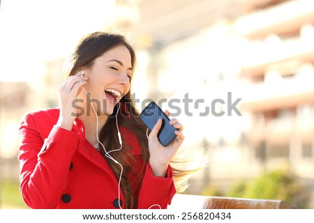 Funny girl listening to the music with earphones from a smart phone with an urban unfocused background - stock photo