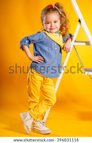 funny girl on bright yellow background. studio. child. Portrait of funny lovely little girl. happy playful child girl - stock photo