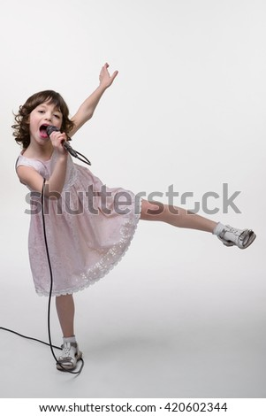 Funny girl's posing with rised hand and leg. Very active and lovely young lady sings in the microphone with cable. Cute dress and shoes for little princesses. - stock photo