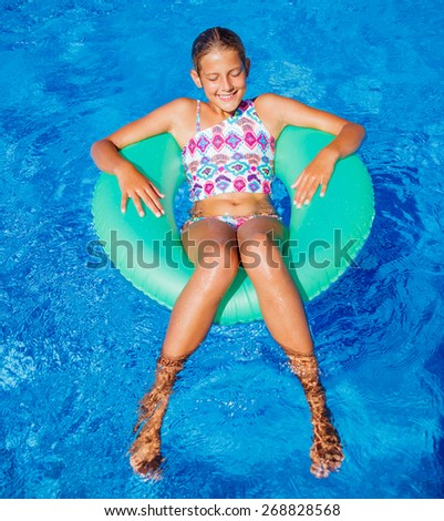 Funny girl swims in a pool in an green life preserver