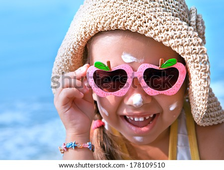 Funny girl wearing sunscreen on your face - stock photo
