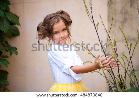 funny girl with beautiful hair in a yellow skirt in the yard
