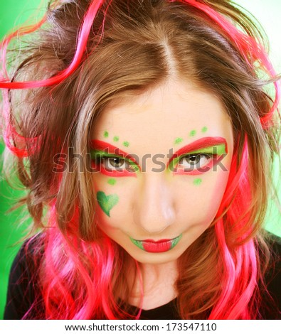 funny girl with crazy make-up over green background - stock photo