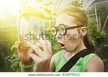 Funny girl with glasses and butterfly in a jar.