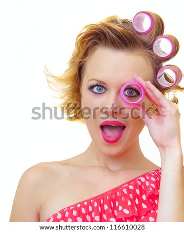 Funny girl with hairstyle looking thro curlers, isolated on white - stock photo