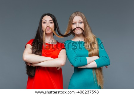 Funny girlfriends making mustache with their hair over gray background